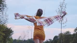 Beautiful young woman with plaid cloth running carefree outside. Slow Motion. Filmed at 250 fps.