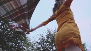 Beautiful young woman with plaid cloth running free outside. Slow Motion. Filmed at 250 fps.