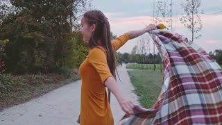 Beautiful young woman with plaid cloth spinning care free outside. Slow Motion. Filmed at 250 fps.