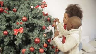 Beauty boy with his mother decorating the christmas tree