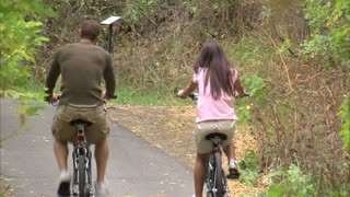 Behind View of Couple Riding Bikes on Path 2