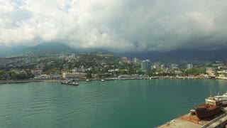 Birds eye view of the city with beautiful beaches and piers, mountains in clouds on the background