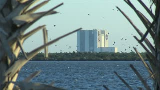 Birds Flying Over Water In Front Of Kennedy Space Center
