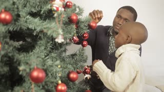 Black boy decorating the christmas tree with his father