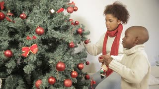 Black boy with his mother decorating the christmas tree