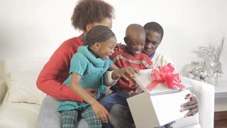 Black family giving holiday gifts