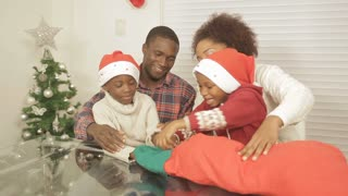 Black family opening christmas gift