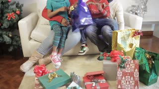 Black family opening their gifts at Christmas, many gifts around