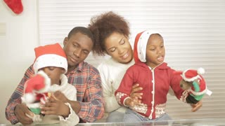 Black family playing with christmas gifts