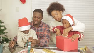 Black family together assembling christmas gift