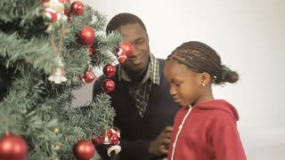 Black girl hugging to her father beside the christmas tree