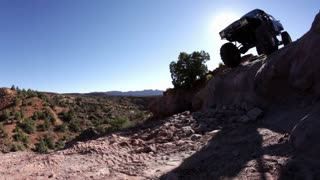 Black Jeep Heads Over Steep Ledge