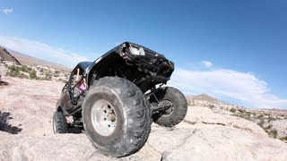Black Jeep Motoring Over Rock Hump