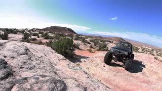 Black Jeep Trying to Clear Rock Hump 1