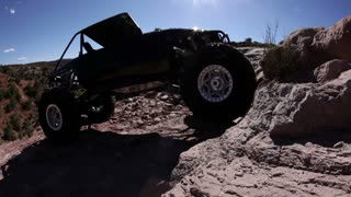 Black Jeep Trying to Climb Steep Ledge