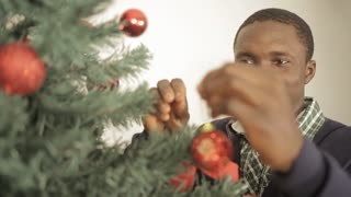 Black man decorating christmas tree