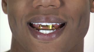 Black Man Holding Pill Between His Teeth