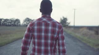 Black man in plaid shirt and blue jeans walks straight on country road