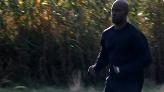 Black Man Running with Trees in Slow Motion
