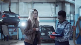 Black mechanic discussing a job sheet with the owner of the vehicle, an attractive blond woman, before he starts a car repair or routine service