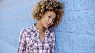 Black Woman Leaning Against Wall