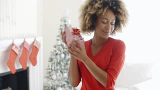 Blissful happy young woman holds a Christmas gift