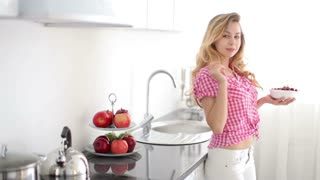 Blond girl in kitchen eating cherries and laughing at camera