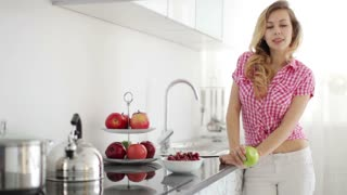 Blond girl standing in kitchen holding apple and smiling at camera