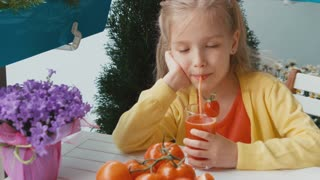 Blonde girl drinking tomato juice and laughing at camera. Thumb up. Ok. Zooming