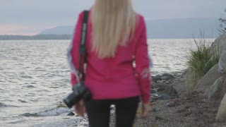 Blonde Girl With Camera Walking Along Rocky Shore