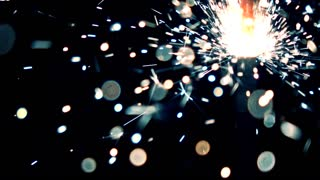 Blue and orange burning sparkler against dark background. Super slow motion shallow focus video
