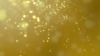 Blurred golden dust slowly falling against yellow background