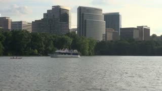 Boat and Kayak on Potomac River with Tall Buildings in the Background