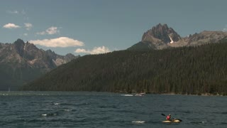 Boaters on Lake in Front of Snow Speckled Rocky Mountain Peaks