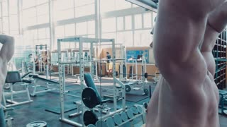 Bodybuilder does movement exercise for back and shoulders, with barbell in gym near mirror. Movement stabilizer shot
