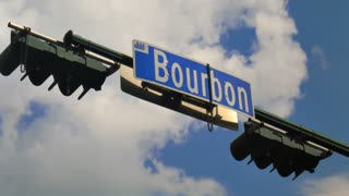Bourbon Street Sign Time-Lapse. The Bourbon Street sign at Canal Street in the French Quarter area of New Orleans, Louisiana. With Mardi Gras beads hanging from it and a nice blue summer sky in the background.