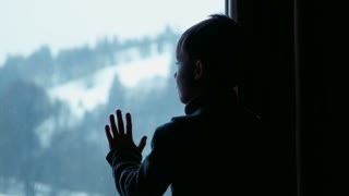 Boy behind window in winter