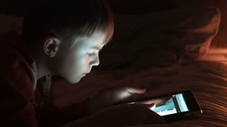 Boy enjoy digital tablet at night