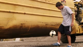 Boy Juggling Soccer Ball in front of Truck