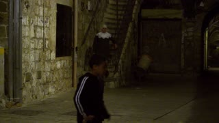 Boy Kicking Soccer Ball In Alley At Night