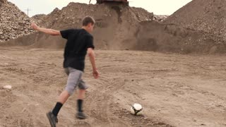 Boy Running and Kicking Soccer Ball