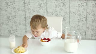 Boy sitting at table and in front of him yogurt, milk and cake