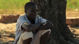Boy Sitting Under a Tree Thinking