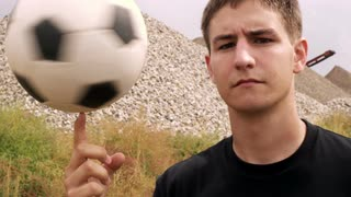 Boy Spinning Soccer Ball on Finger in Slow Motion