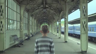 Boy standing on a railway station and waiting for the train