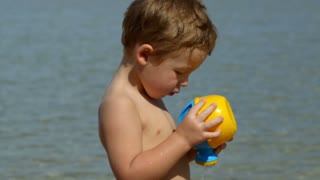 Boy with toy waterpot on the beach, then focus on mother having tea and enjoying sunny day, her son in background