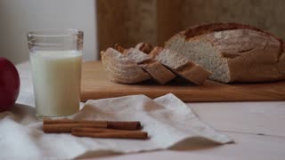 Breakfast food on tablecloth at kitchen table. Milk glass, red apple, and cinnamon sticks on table cloth. Slices of homemade bread on cutting board. Fresh food at breakfast table. Healthy breakfast