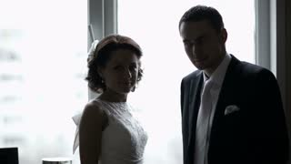 Bride and groom looking out the window. Romantic moments.