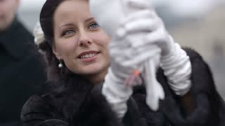 Bride with white wedding pigeon being prepared to release it.