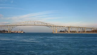 Bridge and Freighter Timelapse. The Blue Water Bridge connecting Port Huron, Michigan, USA with Sarnia, Ontario, Canada. The twin span bridge crosses the St. Clair river and connects Canada with the United States.